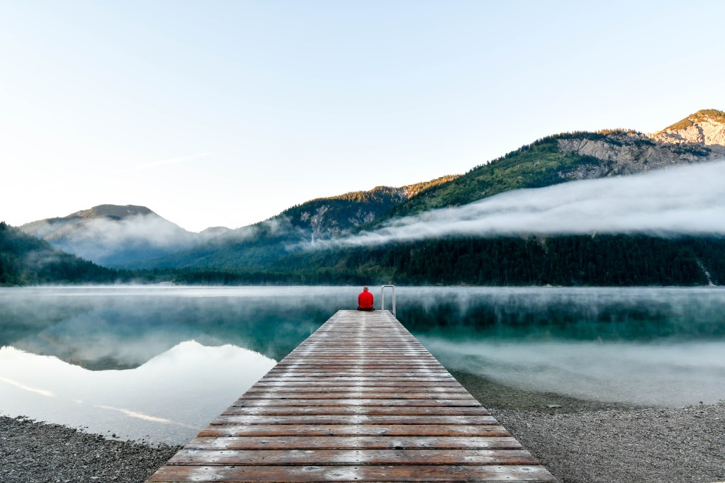 A person sitting on a dock at a lake in the mountains