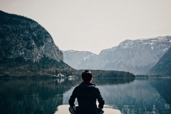Woman meditating on a dock in the middle of a lake in snowing mountains